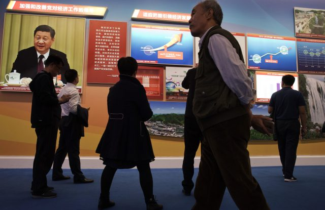 Visitors walk past a chart showing China's soaring GDP since 2012 and a photo of Chinese President Xi Jinping.
