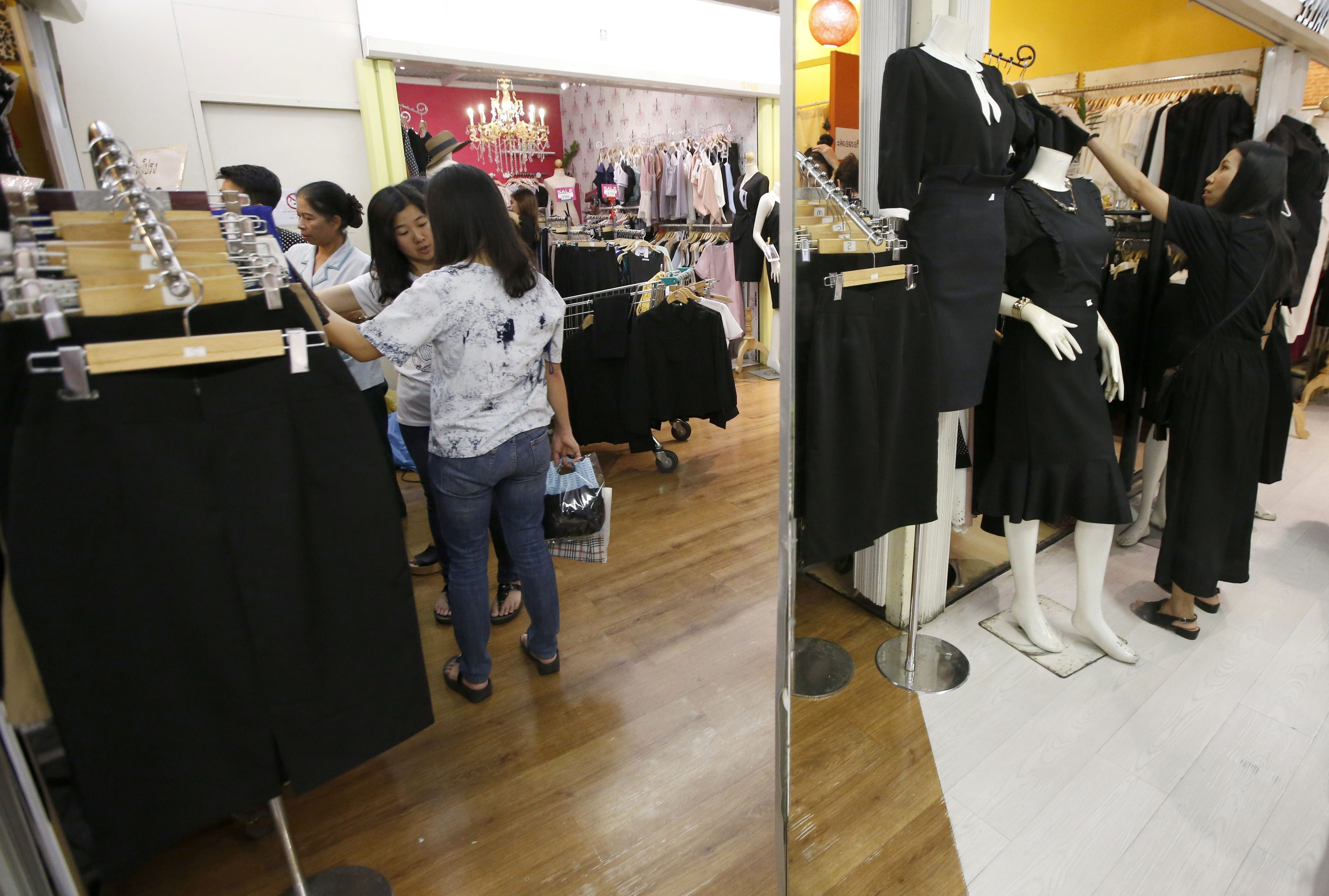 Thai customers are reflected in a mirror while buying black clothing in honor of the late leader.
