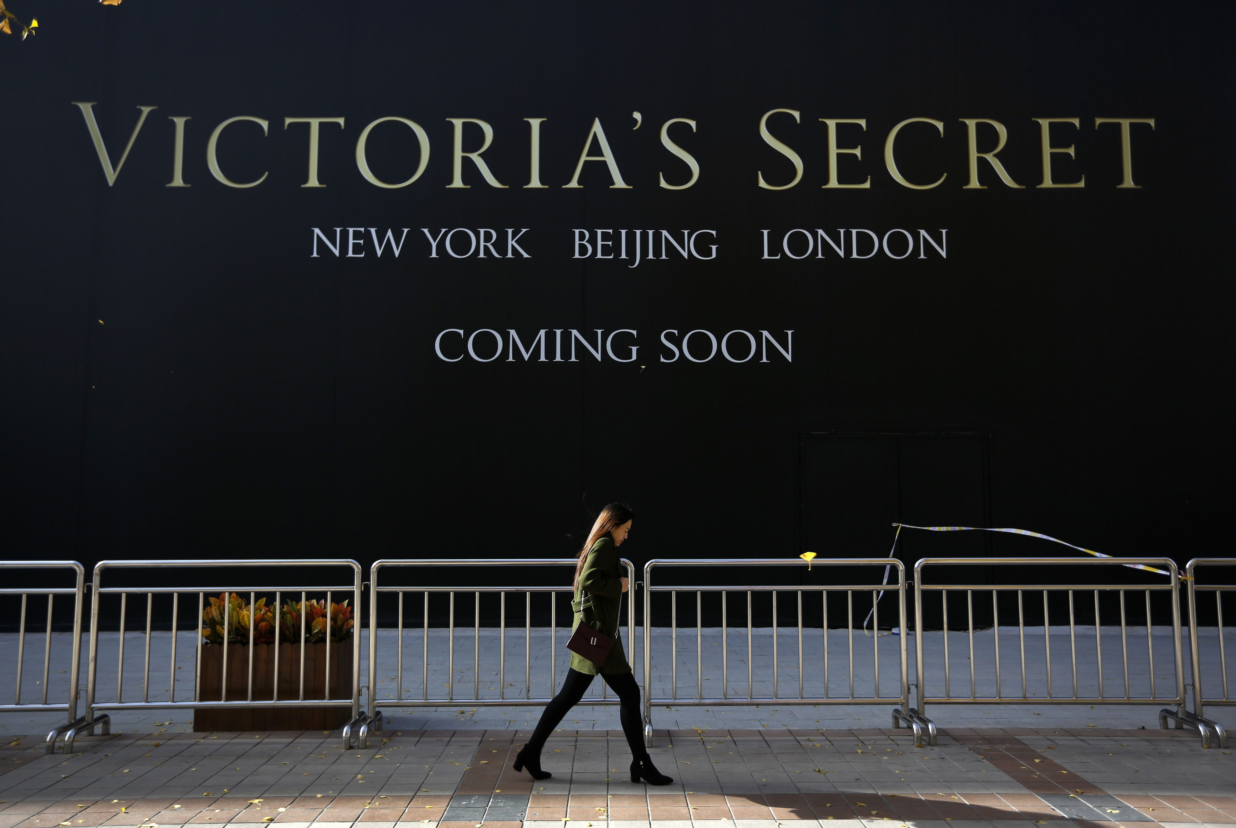 A Chinese woman walks past a Victoria's Secret store under construction in Wangfujing, Beijing.