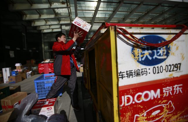 A Chinese messenger transfer packages into his three-wheel delivery cart at a distribution centre for JD.com on Singles' Day.
