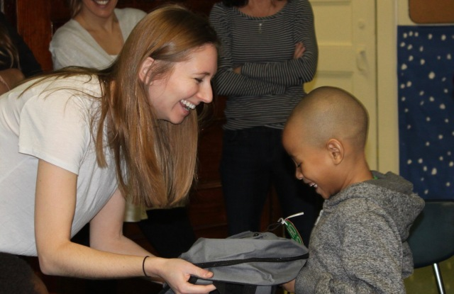Fashion Foundation founder Amanda Munz gives a donated backpack with school supplies and holiday gifts to a student.
