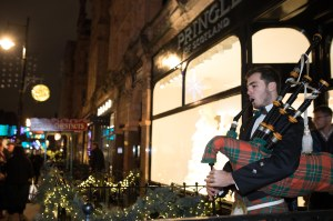 A Scottish piper in front of Pringle of Scotland