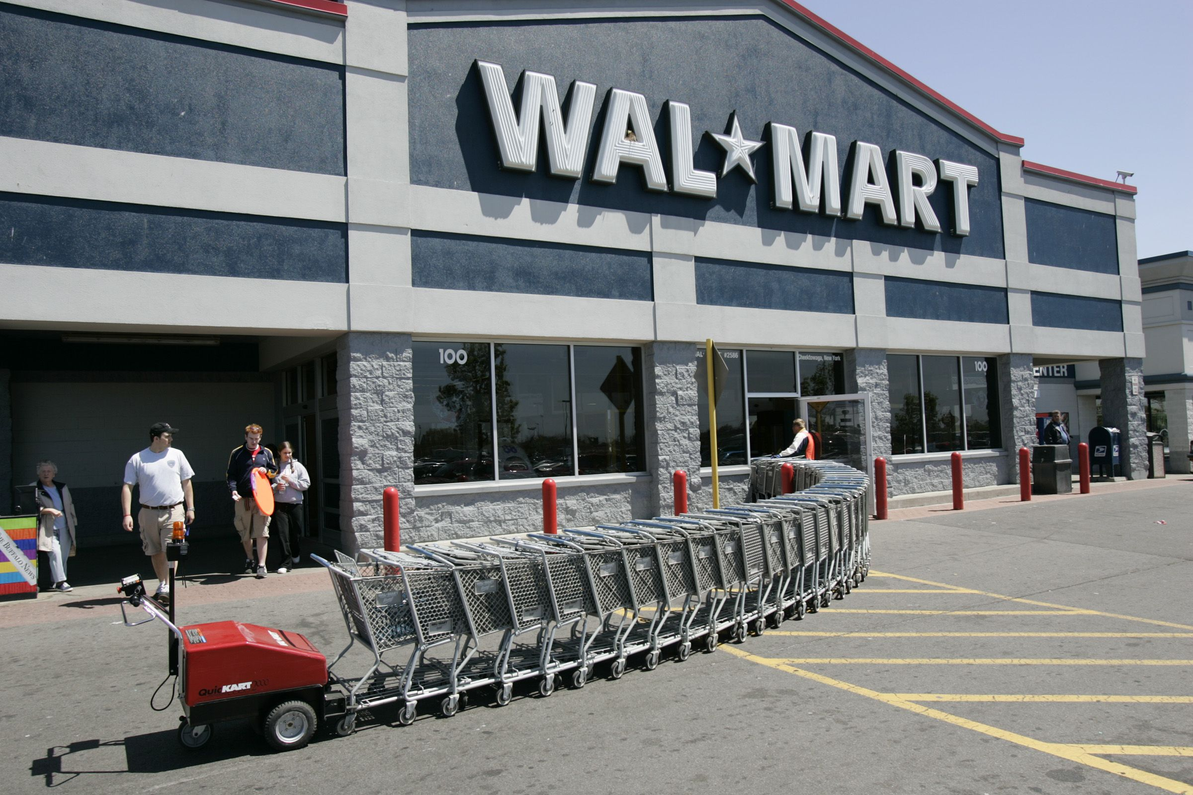 Customers leave Wal-Mart as a machine pushes shopping carts back to the store in Cheektowaga, N.Y. Wal-Mart Stores stores will be phasing out selling Amazon.com's Kindle tablet and e-readers, the world's largest retailer said Thursday, Sept. 20, 2012Wal-Mart Stores-Kindle, CHEEKTOWAGA, USA