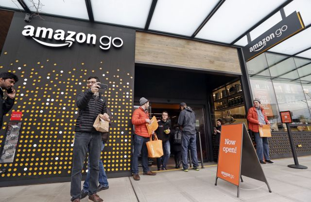 People stand outside an Amazon Go store, in Seattle. More than a year after it introduced the concept, Amazon opened its artificial intelligence-powered Amazon Go store in downtown Seattle on Monday. The store on the bottom floor of the company's Seattle headquarters allows shoppers to scan their smartphone with the Amazon Go app at a turnstile, pick out the items they want and leaveAmazon Go Store, Seattle, USA - 22 Jan 2018