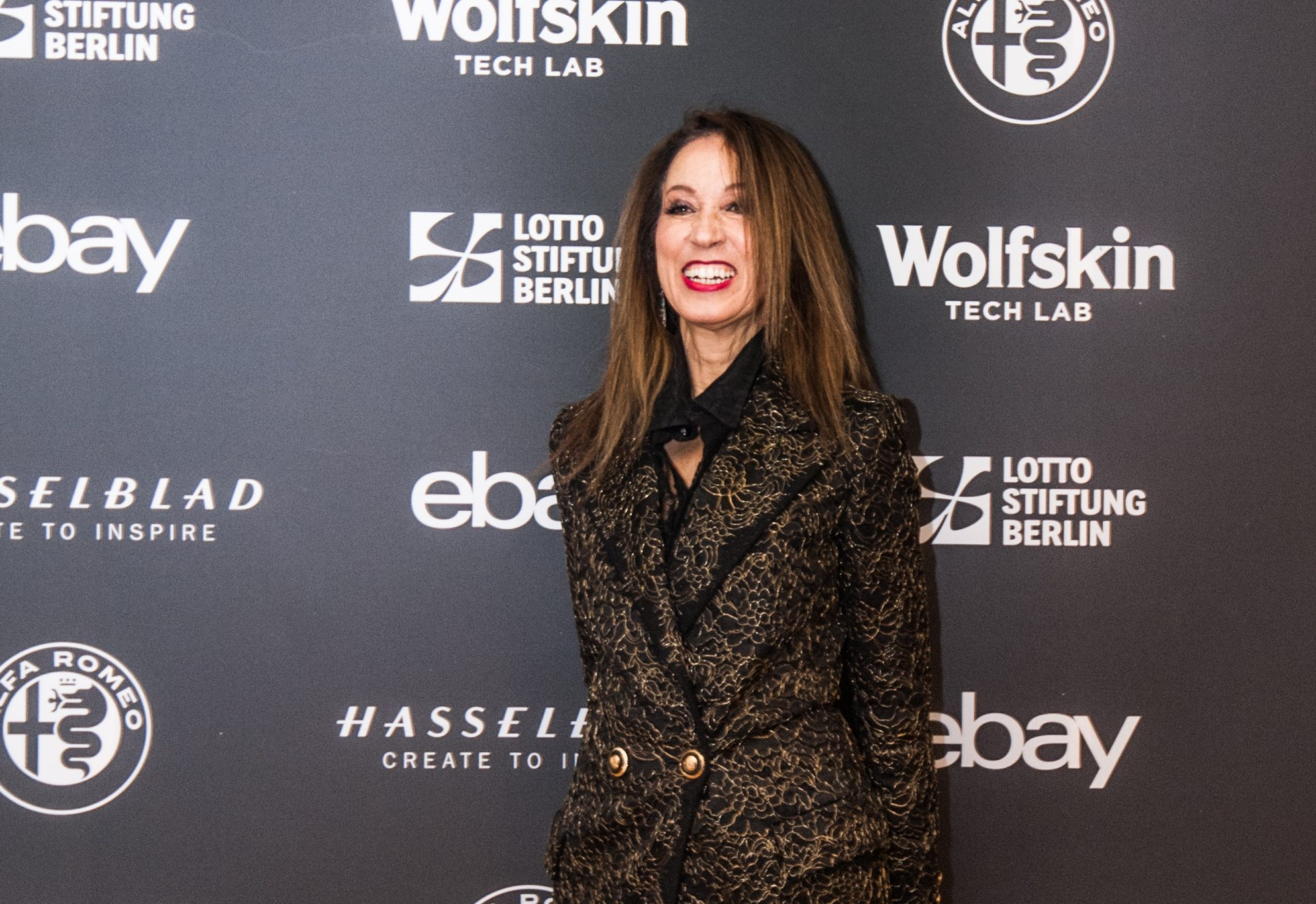 Pat Cleveland wearing an unidentified collector's black and gold Versace coat in Berlin.