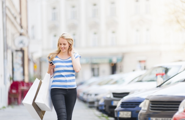 Minimum usage fee is £35Mandatory Credit: Photo by Cultura/REX/Shutterstock (4967034a)MODEL RELEASED, Young woman walking down street, carrying shopping bags, using smartphoneVARIOUS