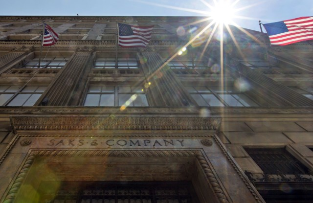 The sun shines through flags on the facade of Saks flagship store on New York's Fifth Avenue, . Saks Inc. agreed to sell itself to Hudson's Bay Co., the Canadian parent of upscale retailer Lord & Taylor, for about $2.4 billion in a deal that will bring luxury to more North American localesSaks Acquisition, New York, USA