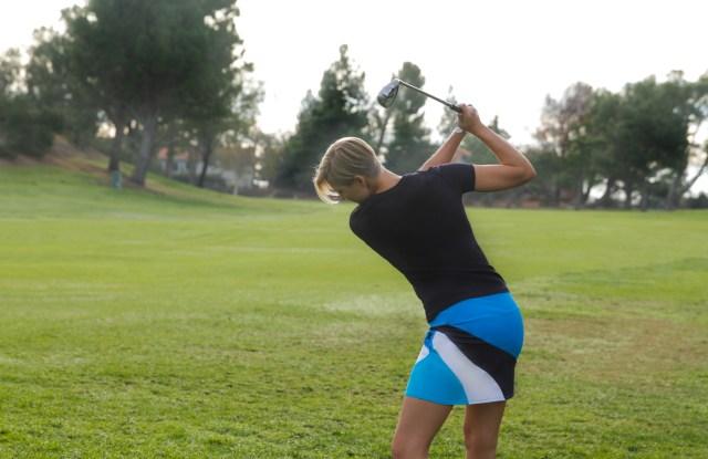 A golfer takes a swing wearing Kinona.