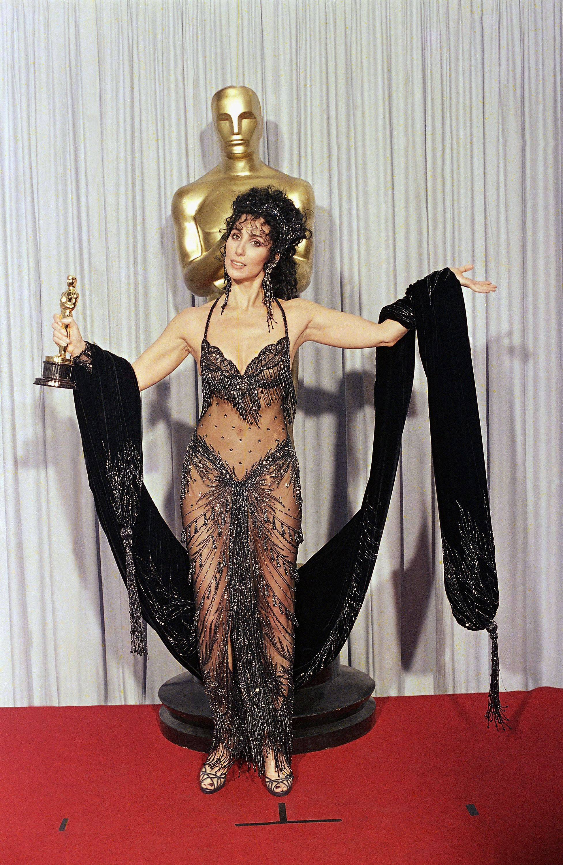 """Cher Cher shows off both her Oscar and Bob Mackie black-sequined gown after winning the award for best actress for her role as the superstitious young widow of """"Moonstruck"""" at the 60th Annual Academy Awards, in Los AngelesOscars Cher Fashion, Los Angeles, USA"""