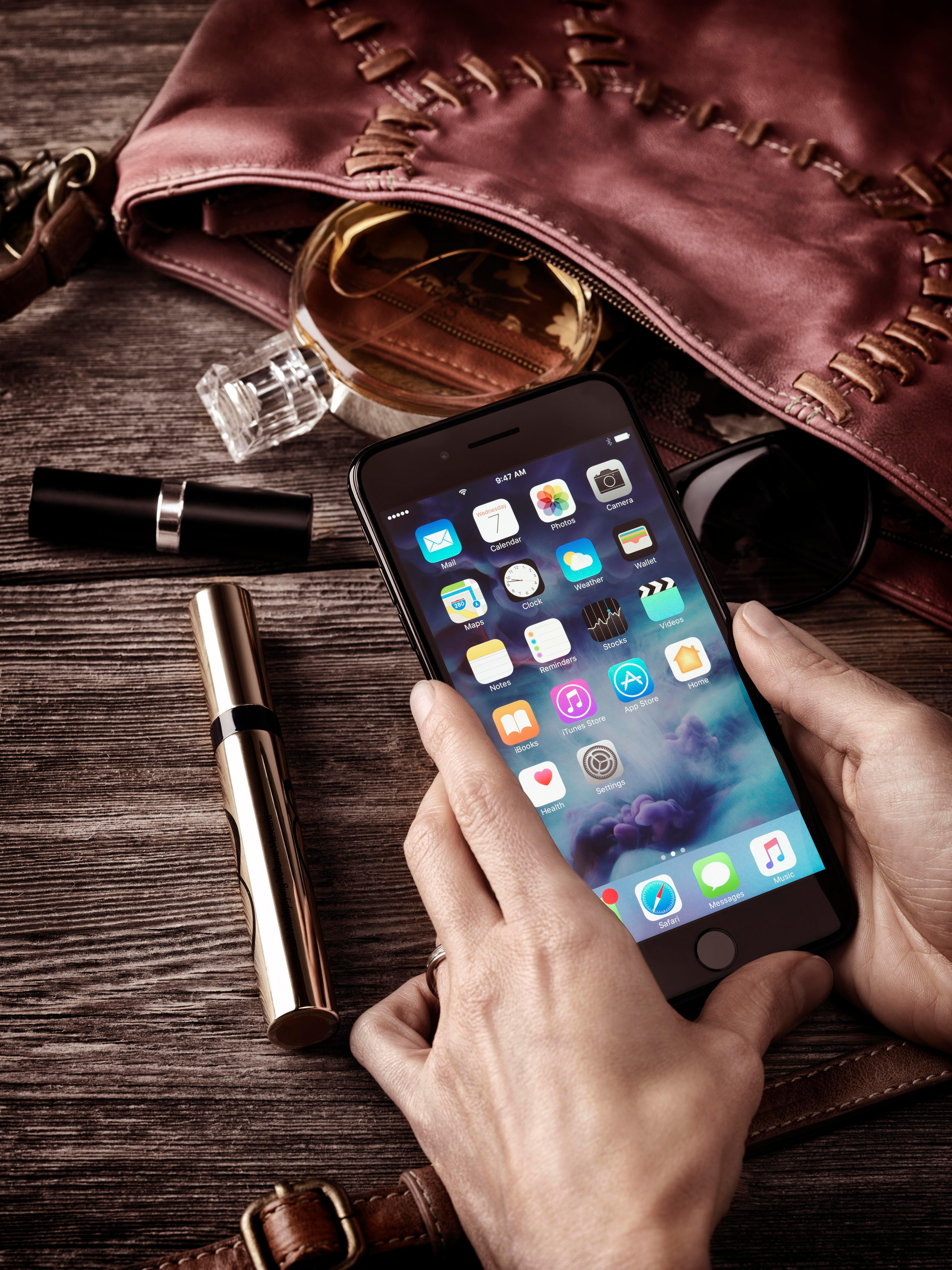 MODEL RELEASED Woman hands holding Apple iPhone 7 Plus, with her purse, makeup and accessories on the table, still lifeVARIOUS