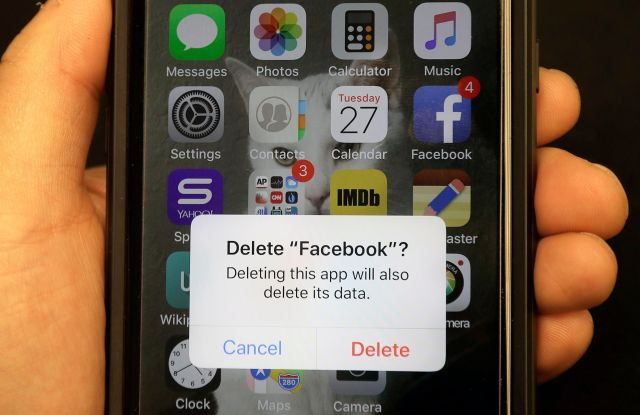 A reporter holds a phone showing the Facebook app in San FranciscoFacebook, San Francisco, USA - 27 Mar 2018