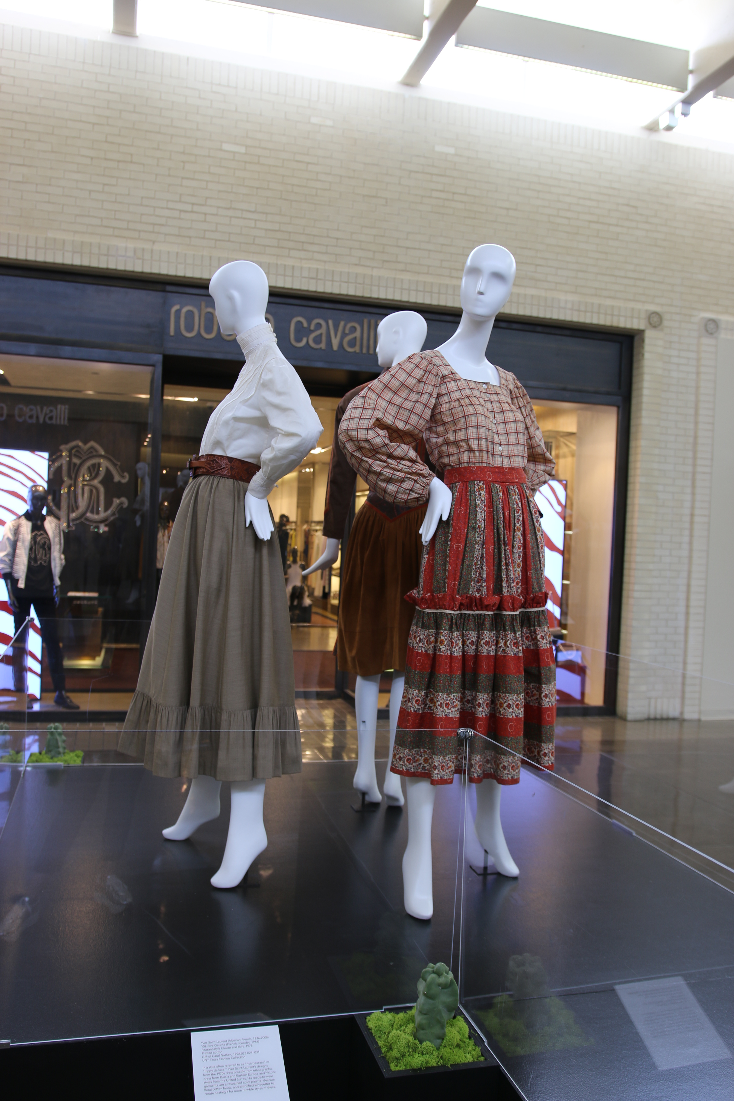 "Outfits by Ralph Lauren, Roberto Cavalli (rear) and Yves Saint Laurent at the ""West Dressed"" exhibit in Dallas."