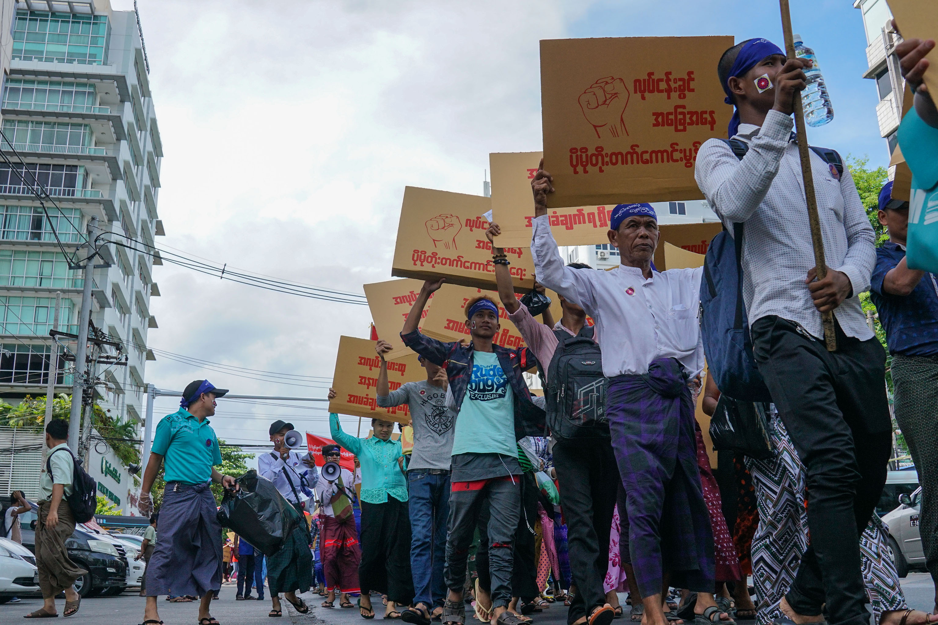 Workers with minimum wage slogans marching in downtown Yangon.
