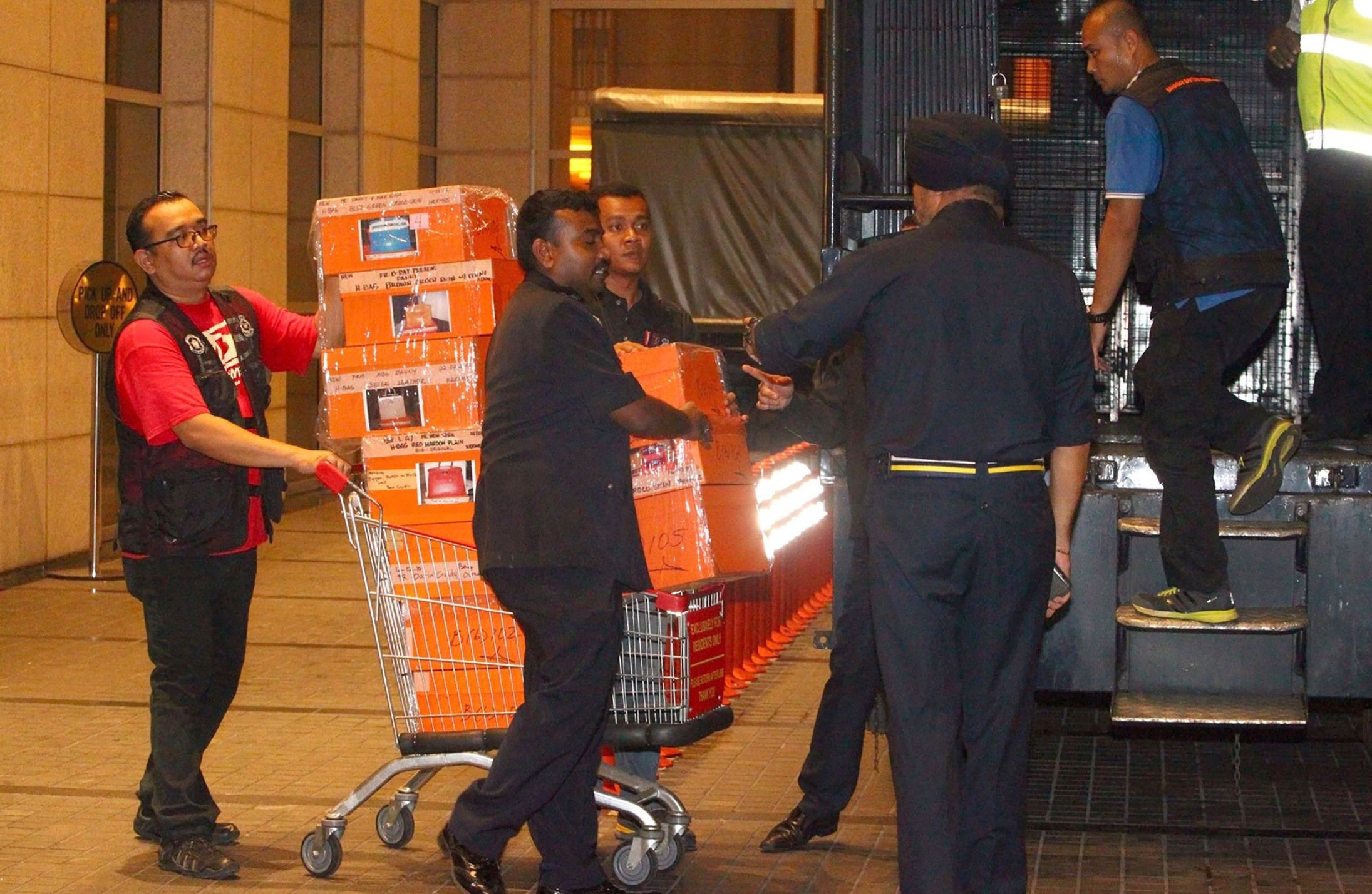 Police load confiscated orange Hermes boxes in a sting operation against Najib Razak.