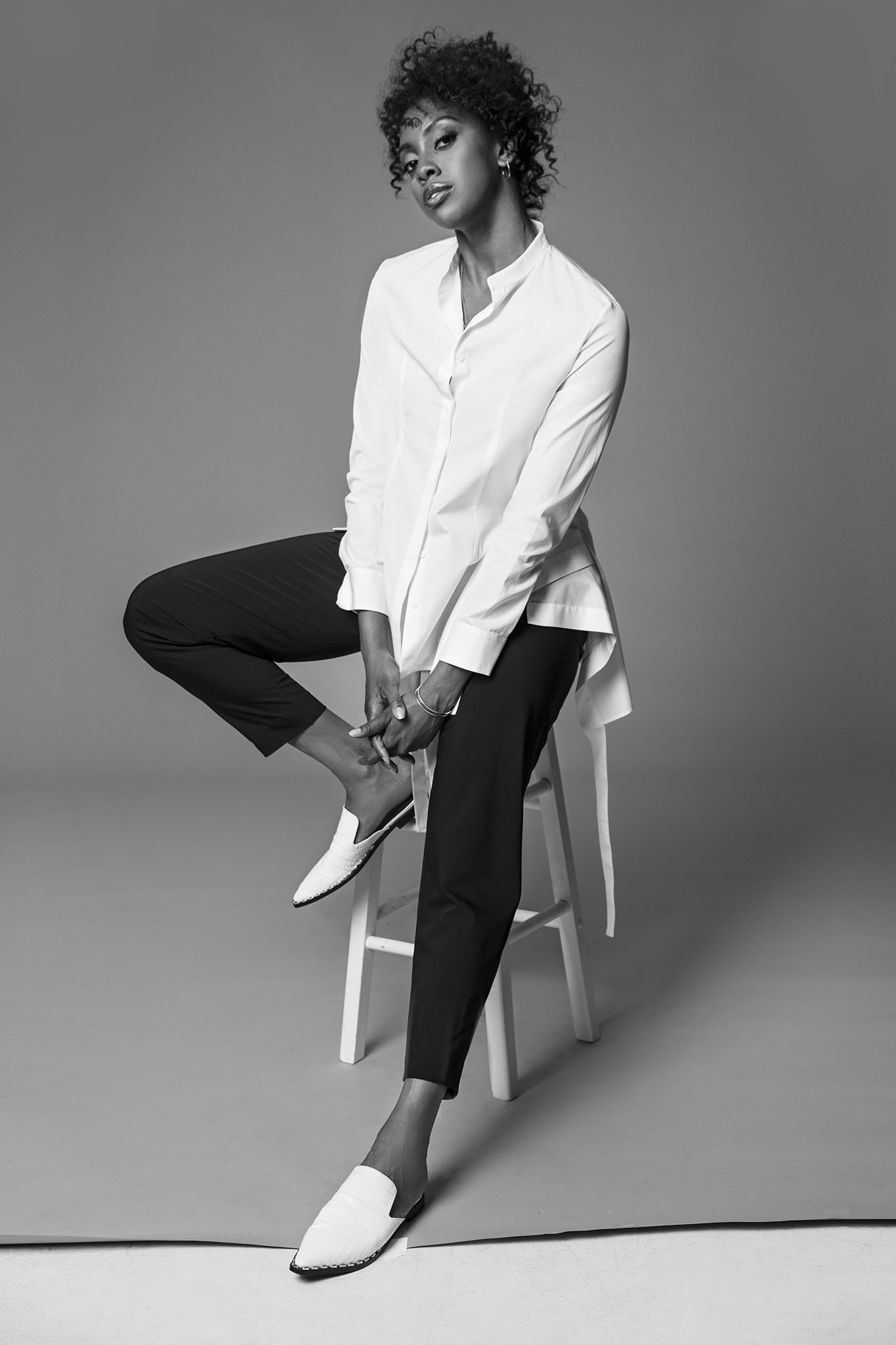 Condola Rashad in Jil Sander's white cotton top and Tibi's wool pants. Paige Novick necklace and earrings, Established Jewelry rings and Sigerson Morrison shoes.