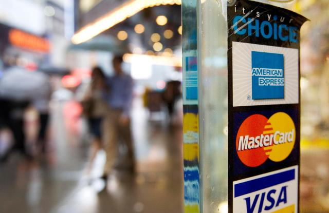 Signs for American Express, Master Card and Visa credit cards are shown on a New York store's doorCredit Cards Minimum Payments, New York, USA
