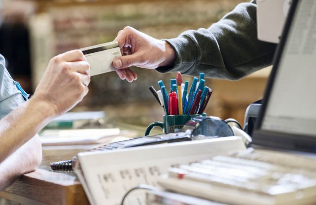 MODEL RELEASED Closeup of hands exchanging a credit card during a retail sale next to a computer at the front desk of a retail shop.VARIOUS