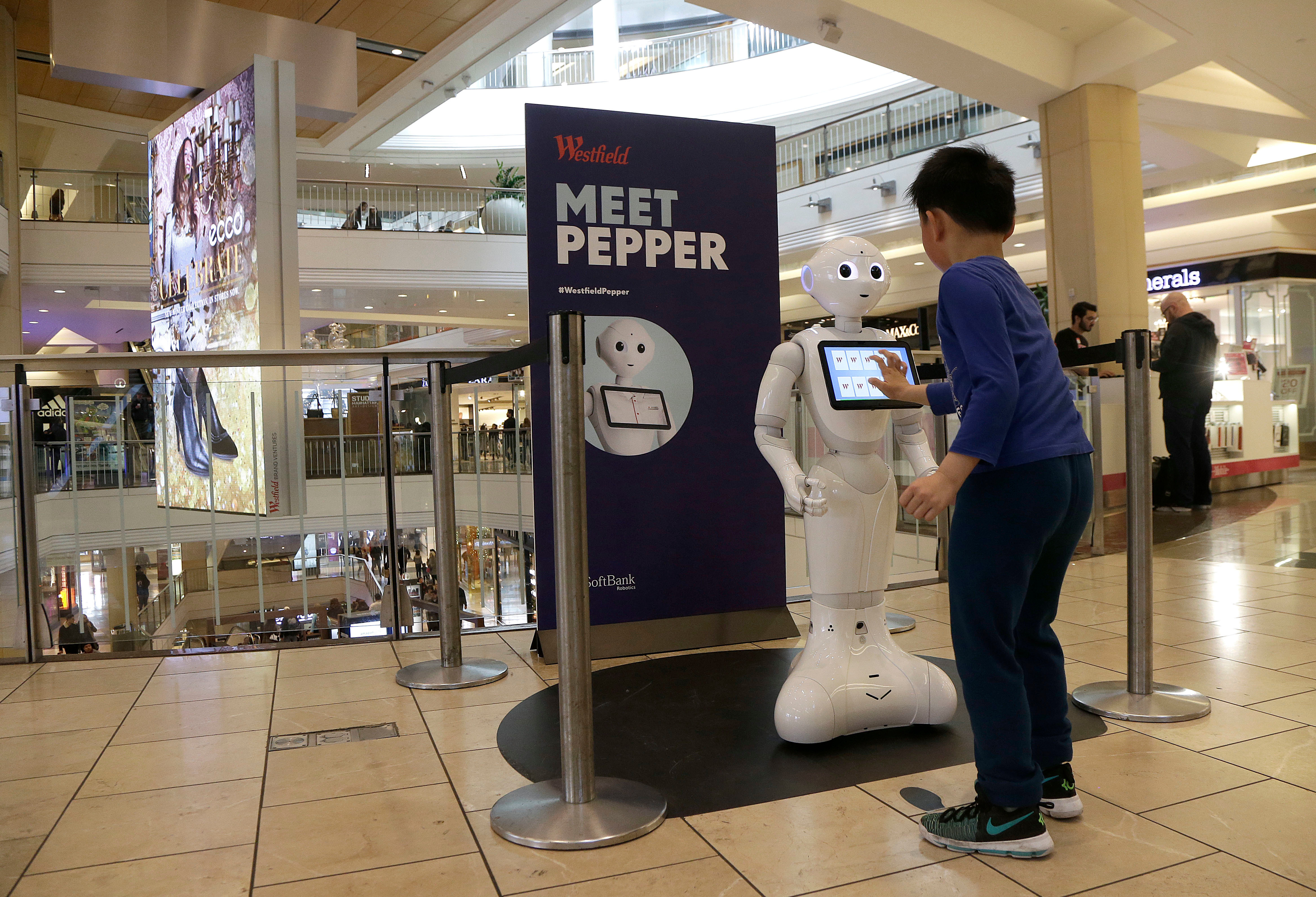 A boy plays with Pepper the robot at Westfield Mall in San Francisco. While merrily chirping, dancing and posing for selfies, Pepper looks like another expensive toy in the San Francisco mall where it will be entertaining shoppers through mid-February. But it would be a mistake to dismiss Pepper as mere child's play, even though kids flock around the 4-foot-tall humanoid as it speaks in a cherubic voice that could belong to either a boy or girlAmbitious Robot, San Francisco, USA - 22 Dec 2016