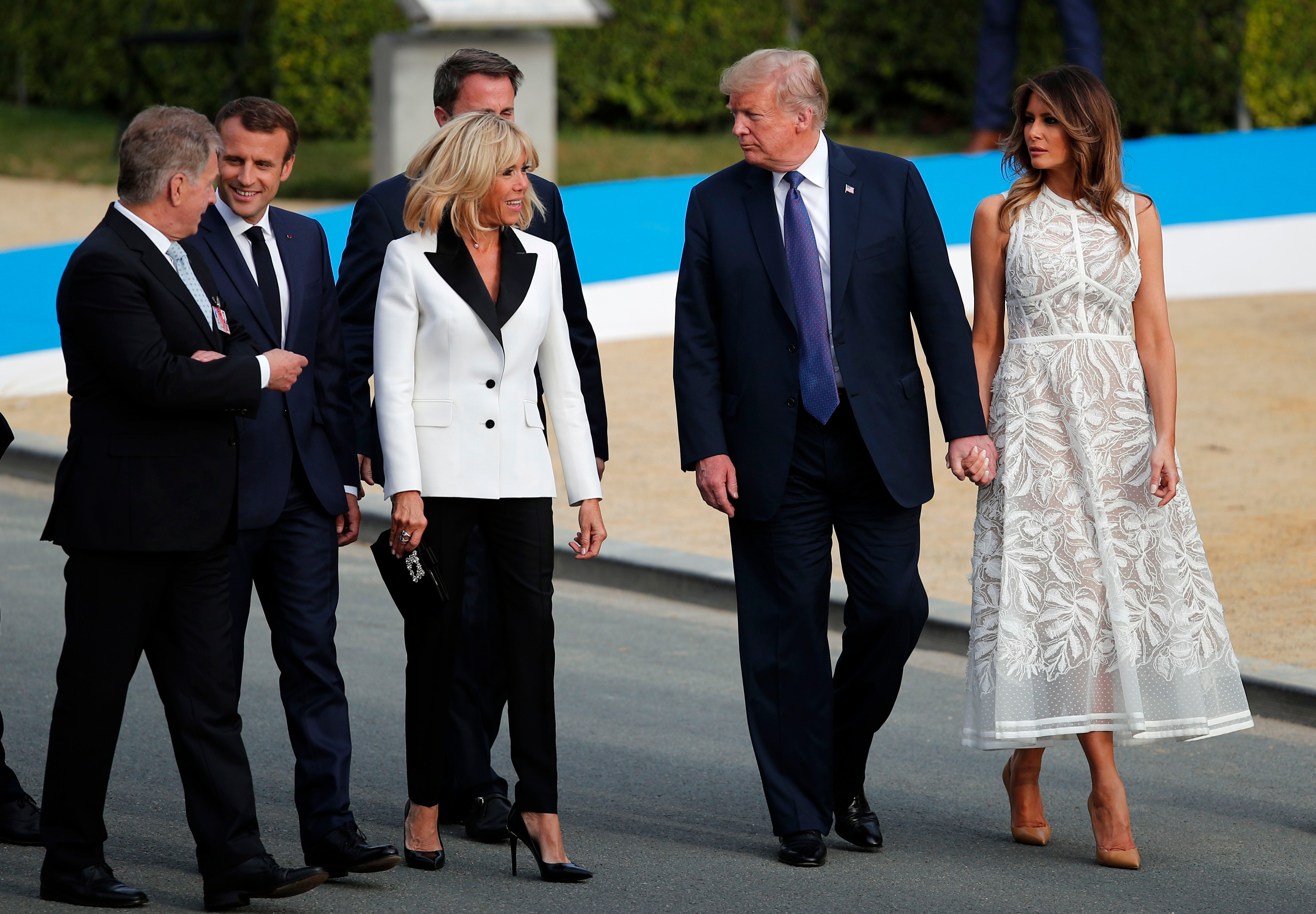 President Donald Trump with U.S. first lady Melania Trump walk with French President Emmanuel Macron and French first lady Brigitte Macron during a group photo of NATO heads of state and government at Park Cinquantenaire in Brussels on . NATO leaders gathered in Brussels Wednesday for a two-day summit to discuss Russia, Iraq and their mission in Afghanistan