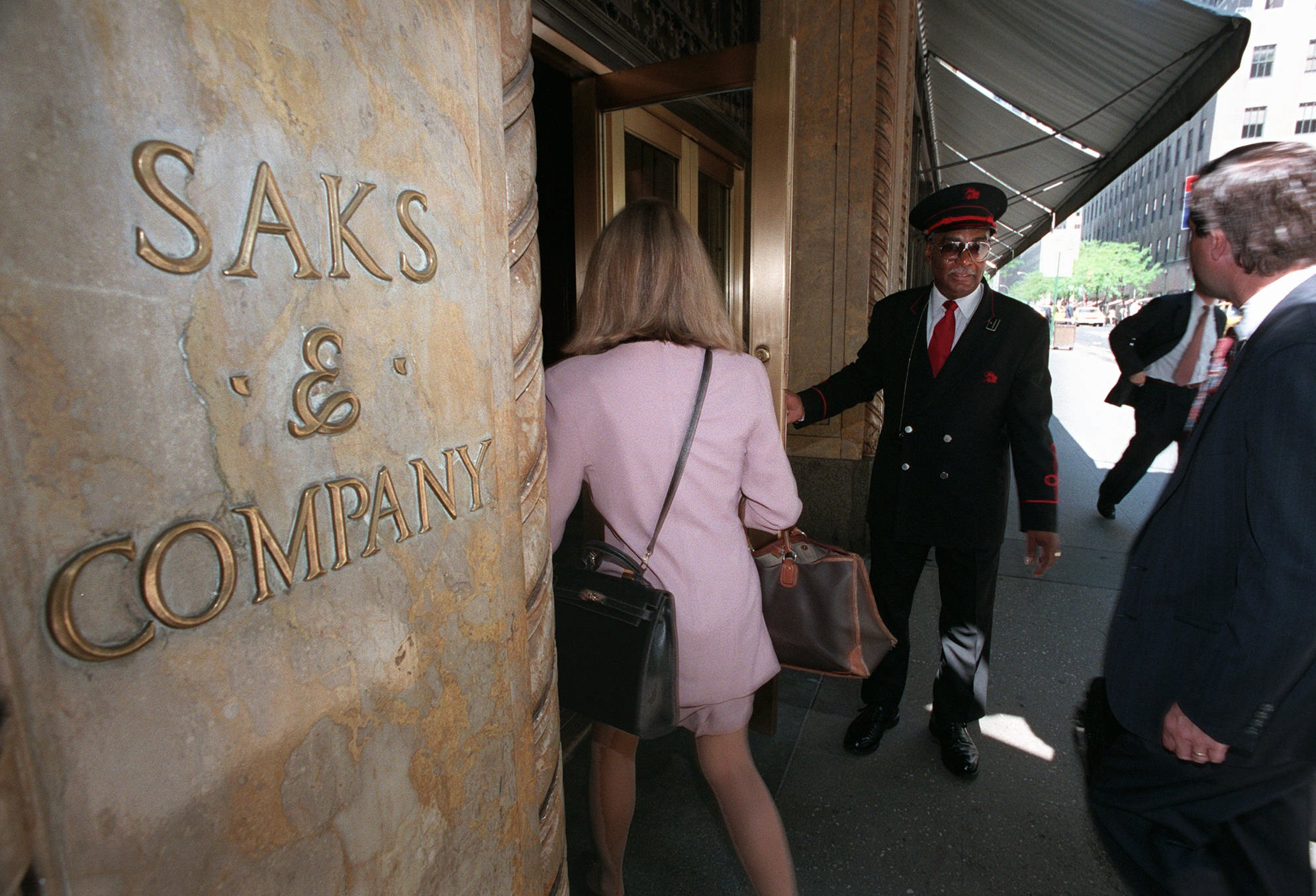 BOND Saks & Company doorman Haywood Bond, a 17-year employee, opens the 50th Street store entrance for customersSAKS FIFTH AVENUE, NEW YORK, USA