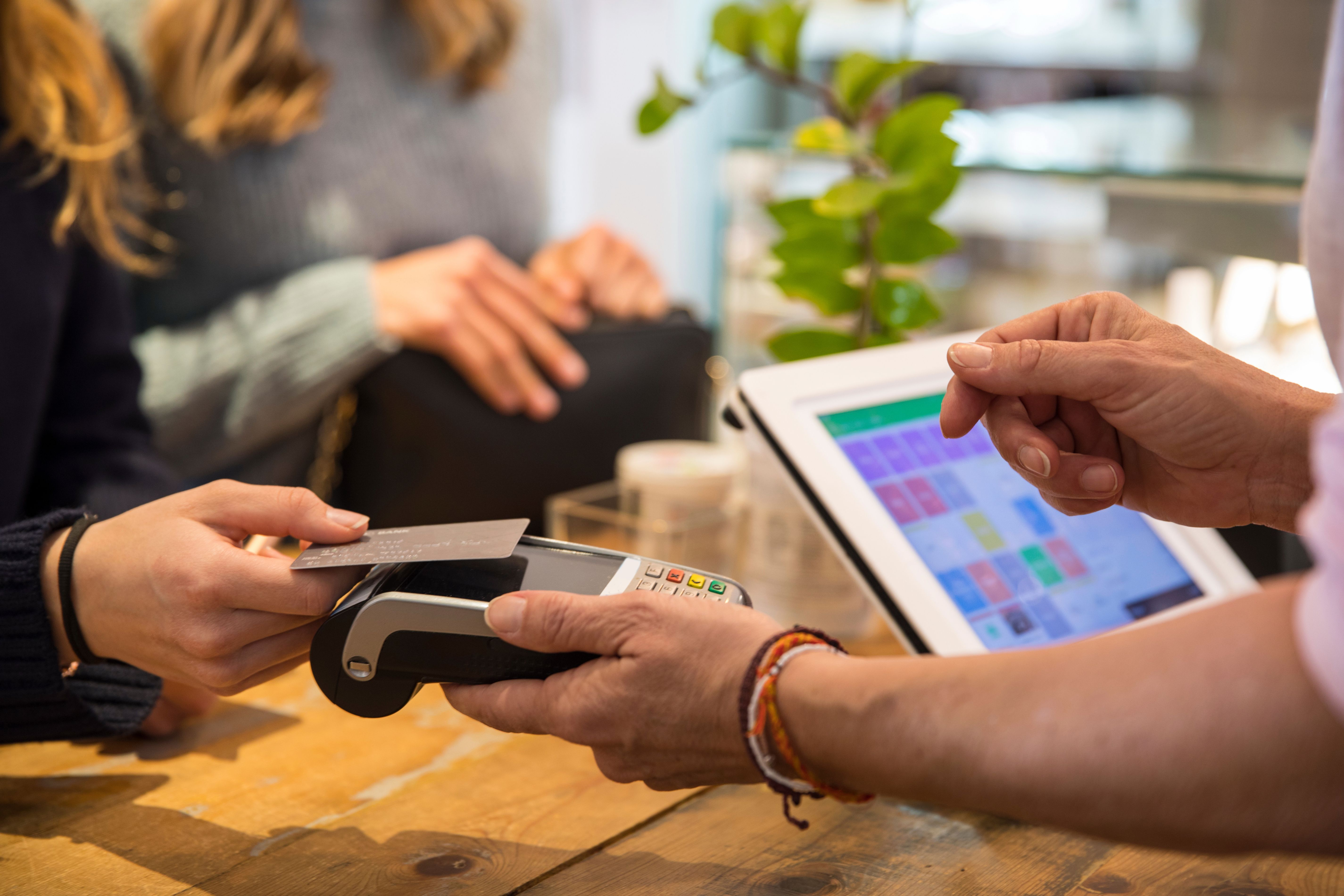 Minimum usage fee is £35Mandatory Credit: Photo by Cultura/REX/Shutterstock (9706678a)MODEL RELEASED, Female customer in shop, paying for goods using credit card on contactless payment machine, mid section, close-upVARIOUS
