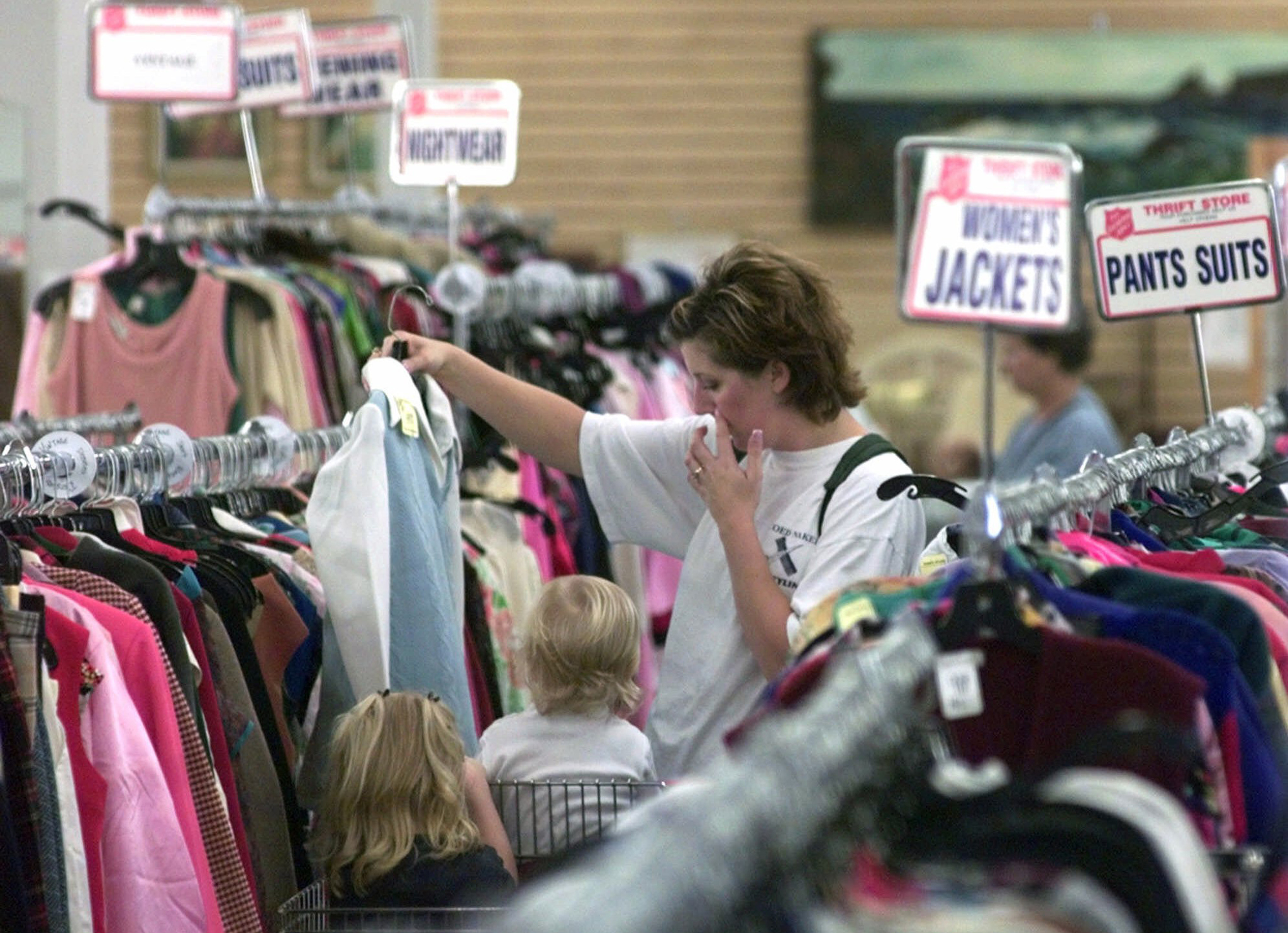 A woman rummages through thrift at Salvation Army.