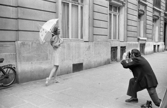 Photographer shooting a model wearing Courreges and holding an umbrella on the streets of Paris *** Local Caption ***