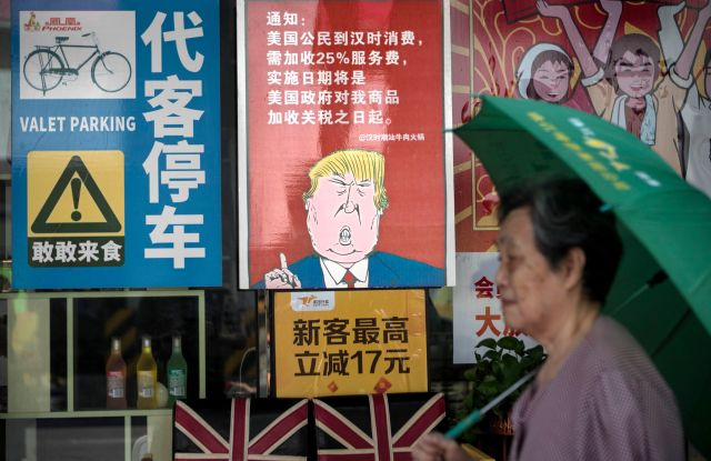 A woman passes by a restaurant with a poster depicting US President Donald J. Trump, stating that all US costumers will be charged 25 percent more than other customers starting from the day president Trump started the trade war with China, in Guangzhou, Guangdong Province, China, 13 August 2018. US President J. Trump announced on 10 July that US is preparing to impose 10 percent tariffs worth 200 billion US dollars on imported goods from China. These tariffs would affected mainly consumer goods.US-China trade war, Guangzhou - 13 Aug 2018