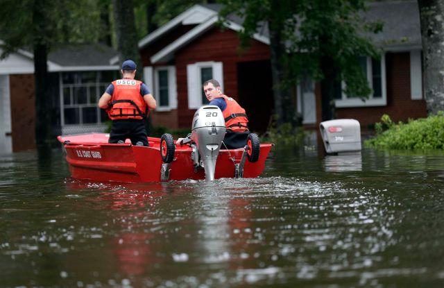 Members of the U.S. Coast Guard check on a neighborhood in Lumberton, N.C., following flooding from Hurricane FlorenceTropical Weather North Carolina, Lumberton, USA - 16 Sep 2018