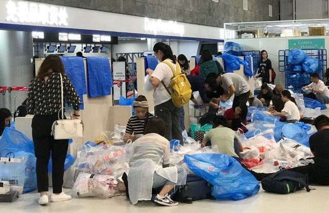 "Inside the Jeju airport in South Korea, a designated ""repackaging area"" where many Mainland Chinese rip open their duty free purchases and take off their packaging. Jeju is a 90 minute flight from Shanghai and a key destination for daigou sellers."
