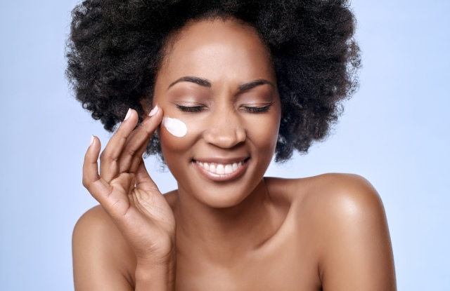 Beautiful black african model with flawless skin smooth complexion applying moisturiser face cream to her cheek, beauty cosmetics skincare concept; Shutterstock ID 324717266; Usage (Print, Web, Both): both; Issue Date: 2 oct; Comments: wwd