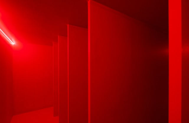 A Spatial environment in red light by Lucio Fontana.