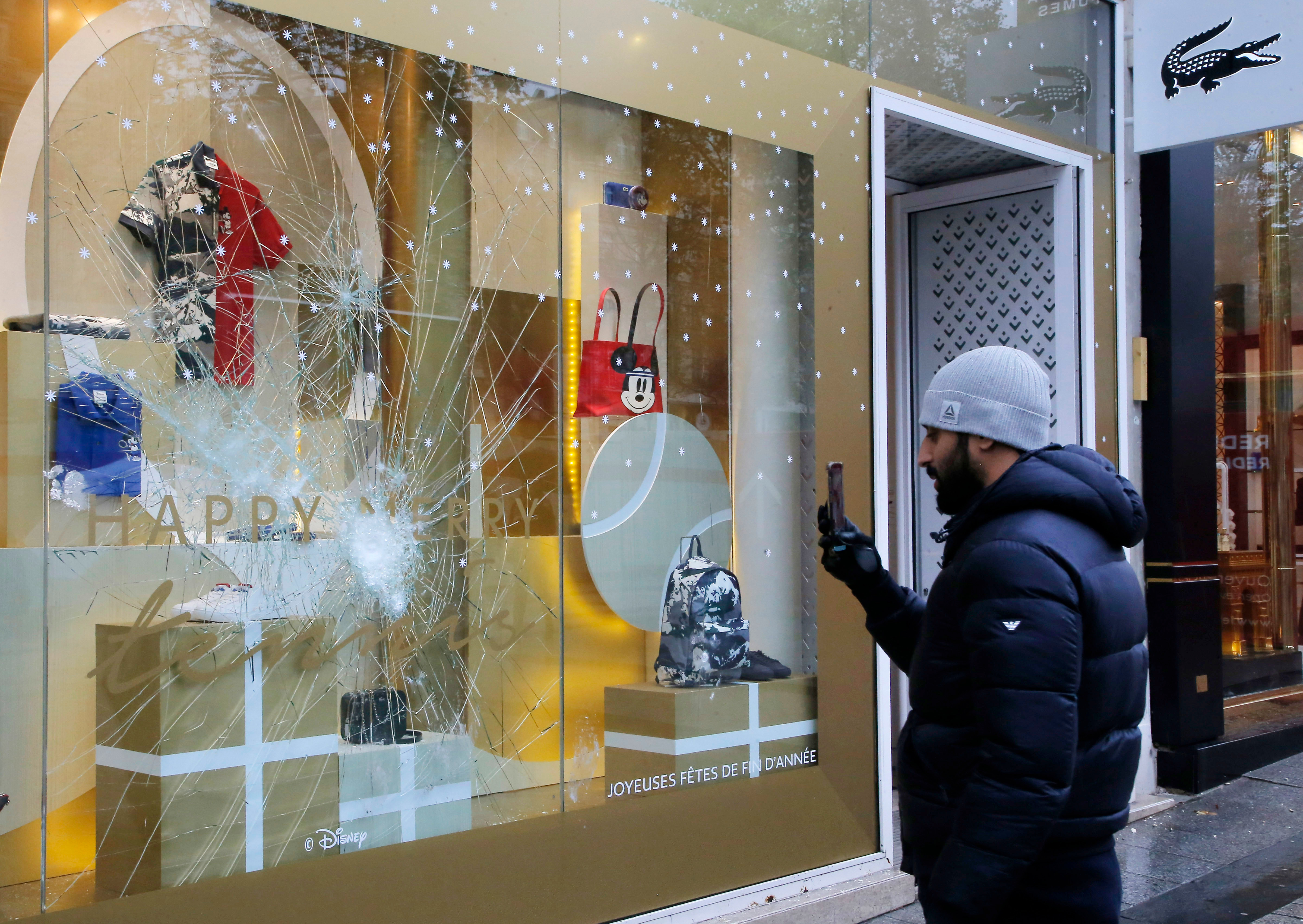 A man takes a photograph with his mobile phone of a smashed window at the Champs Elysees avenue in Paris, France, in the aftermath of a protest against the rising of the fuel taxes. French President Emmanuel Macron has condemned violence by protesters at demonstrations against rising fuel taxes and his governmentGas Price Protests Aftermath, Paris, France - 25 Nov 2018
