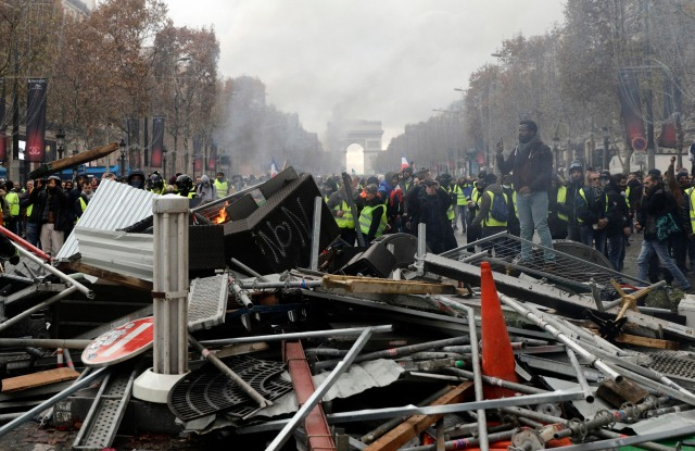 Demonstrators, called the yellow jackets, set up a makeshift barricade on the famed Champs Elysees avenue, during a protest against the rising of the fuel taxes, in Paris, France, . French police fired tear gas and water cannons to disperse demonstrators in Paris Saturday, as thousands gathered in the capital and staged road blockades across the nation to vent anger against rising fuel taxes and Emmanuel Macron's presidencyGas Price Protests, Paris, France - 24 Nov 2018