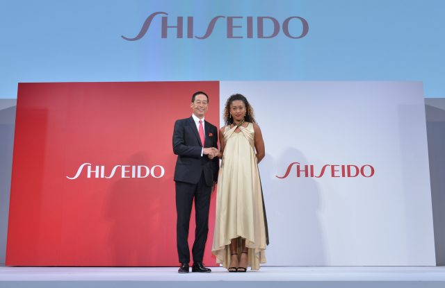 Shiseido's Masahiko Uotani stands with Naomi Osaka at the press conference announcing her ambassadorship for the beauty company.