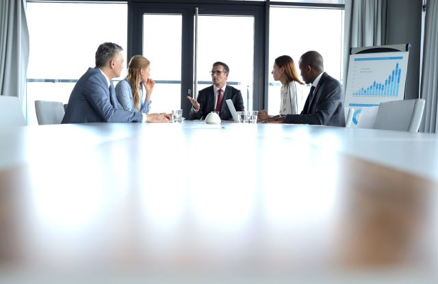 MODEL RELEASED Multi-ethnic business people having discussion at table in board roomVARIOUS