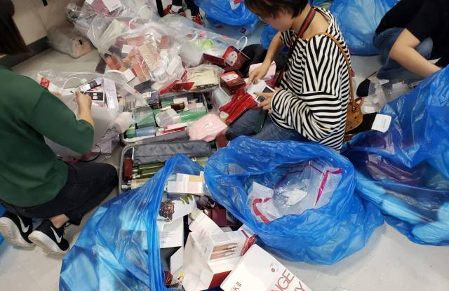 A gray market trader sorts through duty free purchases at Jeju airport.
