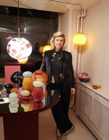 Artist Helle Mardahl stands alongside the glassworks designs in her studio.