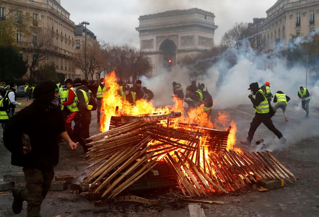 Demonstrators run by a burning fire near the Arc de Triomphe during a demonstration Saturday, Dec.1, 2018 in Paris. Paris police say at least 63 people have been arrested in violent clashes between protesters and police amid nationwide demonstrations against rising taxes and President Emmanuel Macron's policiesGas Price Protests, Paris, France - 01 Dec 2018