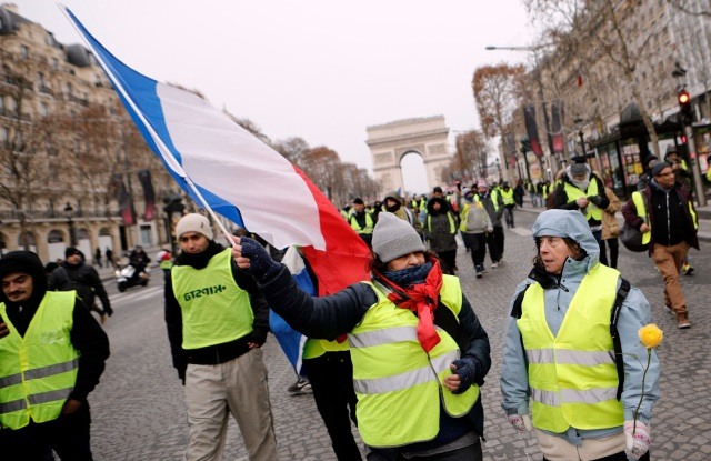 "Demonstrators wearing yellow vests walk down the Champs-Elysees avenue, in Paris. A strong police presence has deployed in Paris before planned demonstrations by the ""yellow vest"" protesters, with authorities repeating calls for calm after previous violent protests and riotingProtests, Paris, France - 15 Dec 2018"