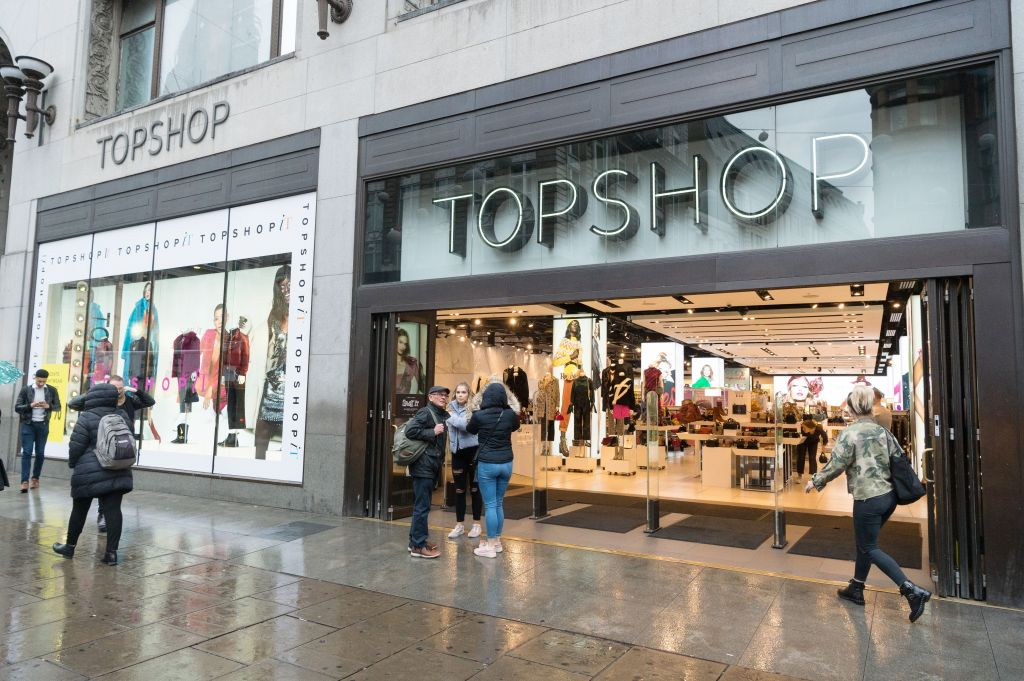 A woman holding an umbrella walks past the Topshop flagshop store in Oxford Circus as it opens for customers.Top Shop business continues after Sir Phillip Green Allegations, London, UK - 26 Oct 2018