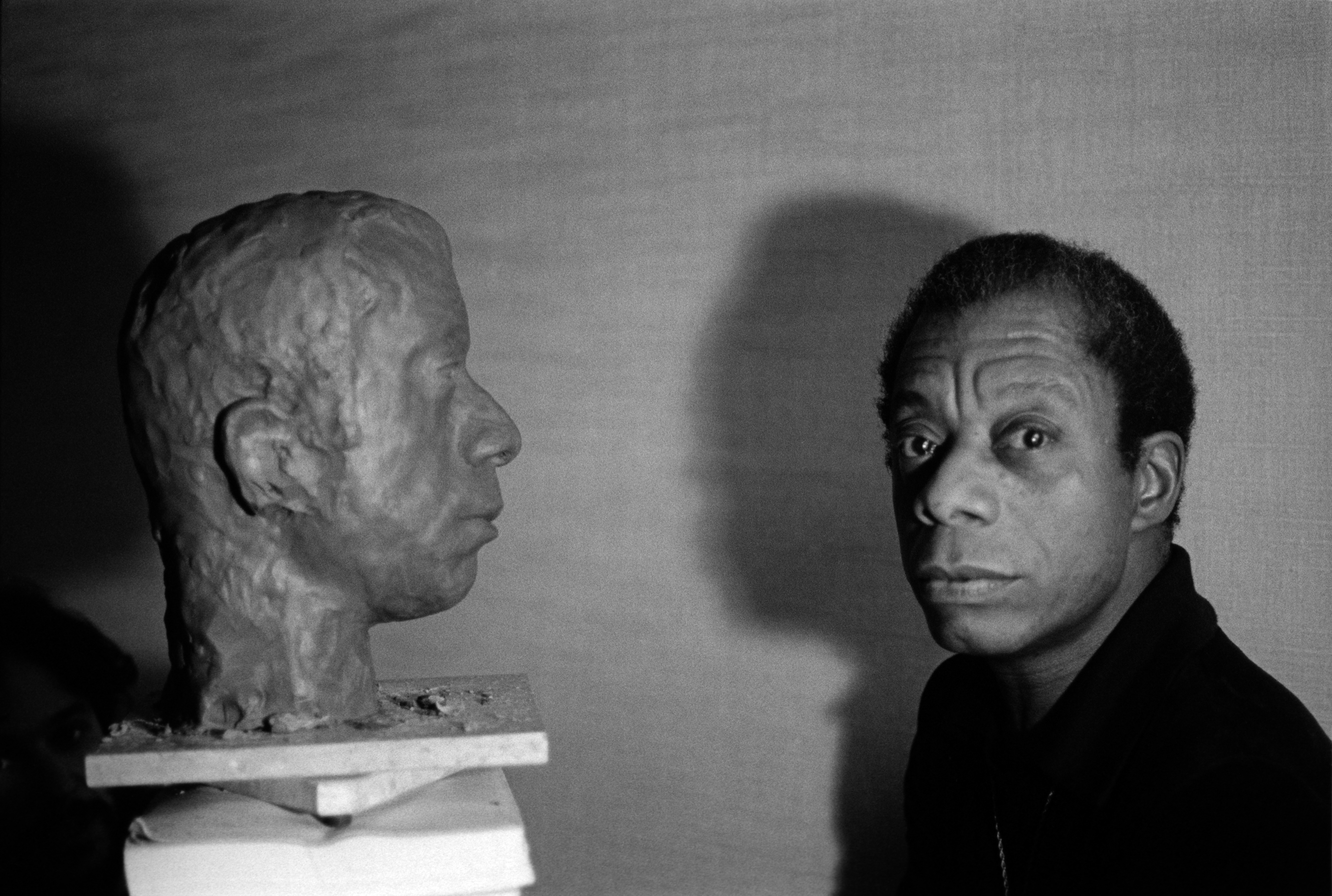 James Baldwin with the bust of his head by American artist, Lawrence Wolhandler - in his hotel room, rue des Grands Augustins, Paris, France. 1975. James Baldwin avec le buste de sa tte fait par l'artiste Americain, Lawrence Wolhandler - dans sa chambre d'h™tel Rue des Grands Augustins, Paris, France. 1975.