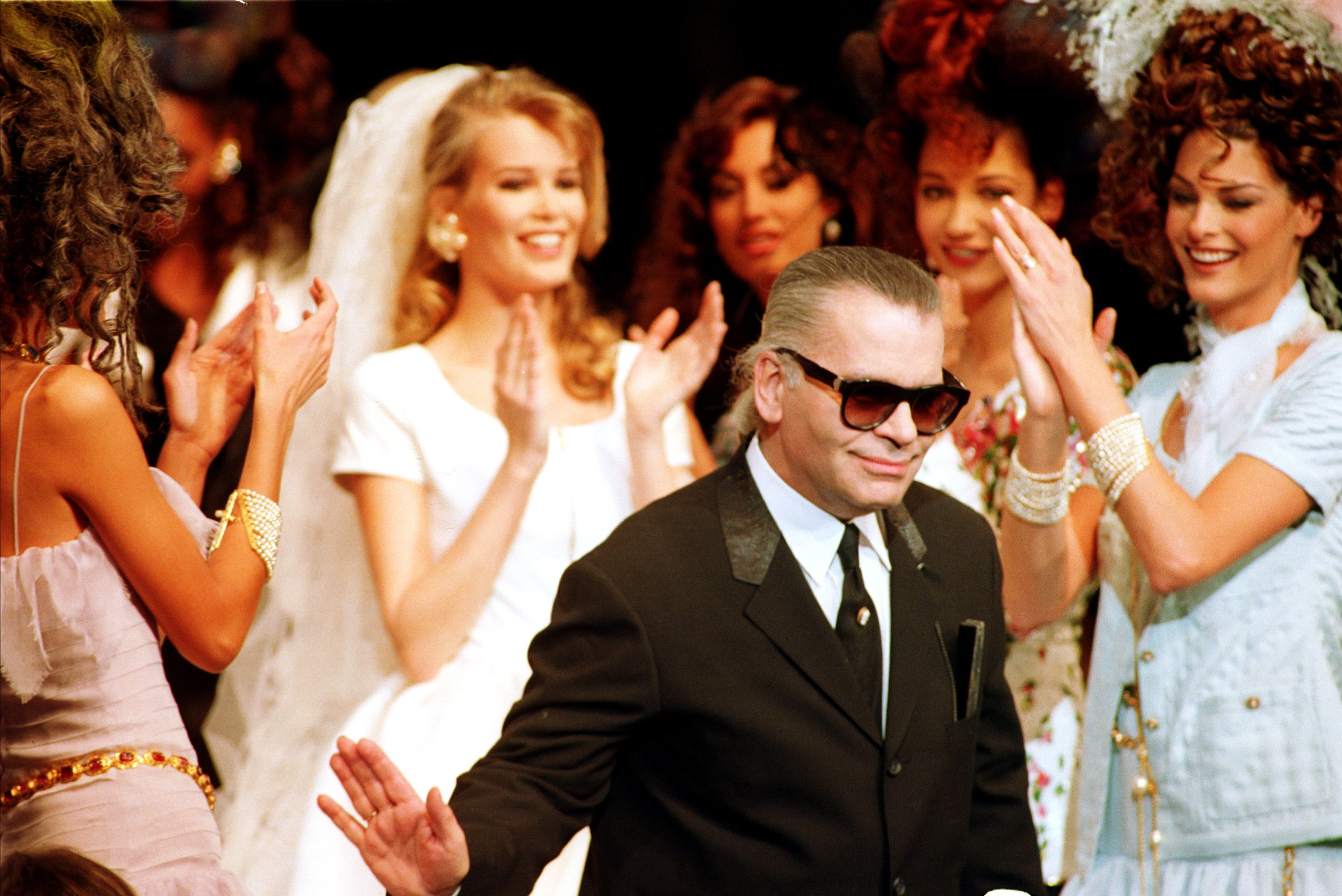Lagerfeld Evangelista Schiffer German designer Karl Lagerfeld acknowledges cheers from the audience and from his models after presentation of the show he designed for French fashion house Chanel in Paris, France, . The presentation is for the 1992 spring and summer haute couture collection. At left, in bridal wear, is German model Claudia Schiffer, and at right is Canadian model Linda EvangelistaFASHION CHANEL LAGERFELD, PARIS, France