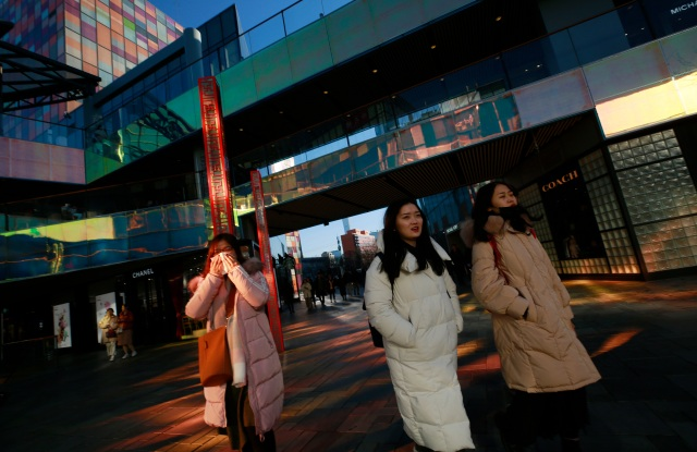 People walk through the Sanlitun Taikooli mall in Beijing.