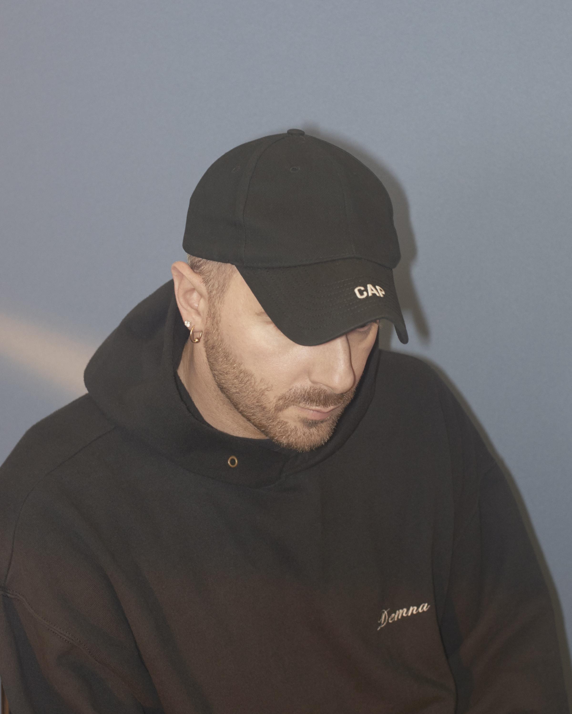 Designer Demna Gvasalia in his signature black baseball cap and oversize hoodie.