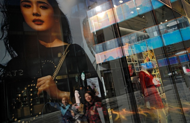 Chinese shoppers are reflected as they walk past a fashion boutique's windows in Beijing.