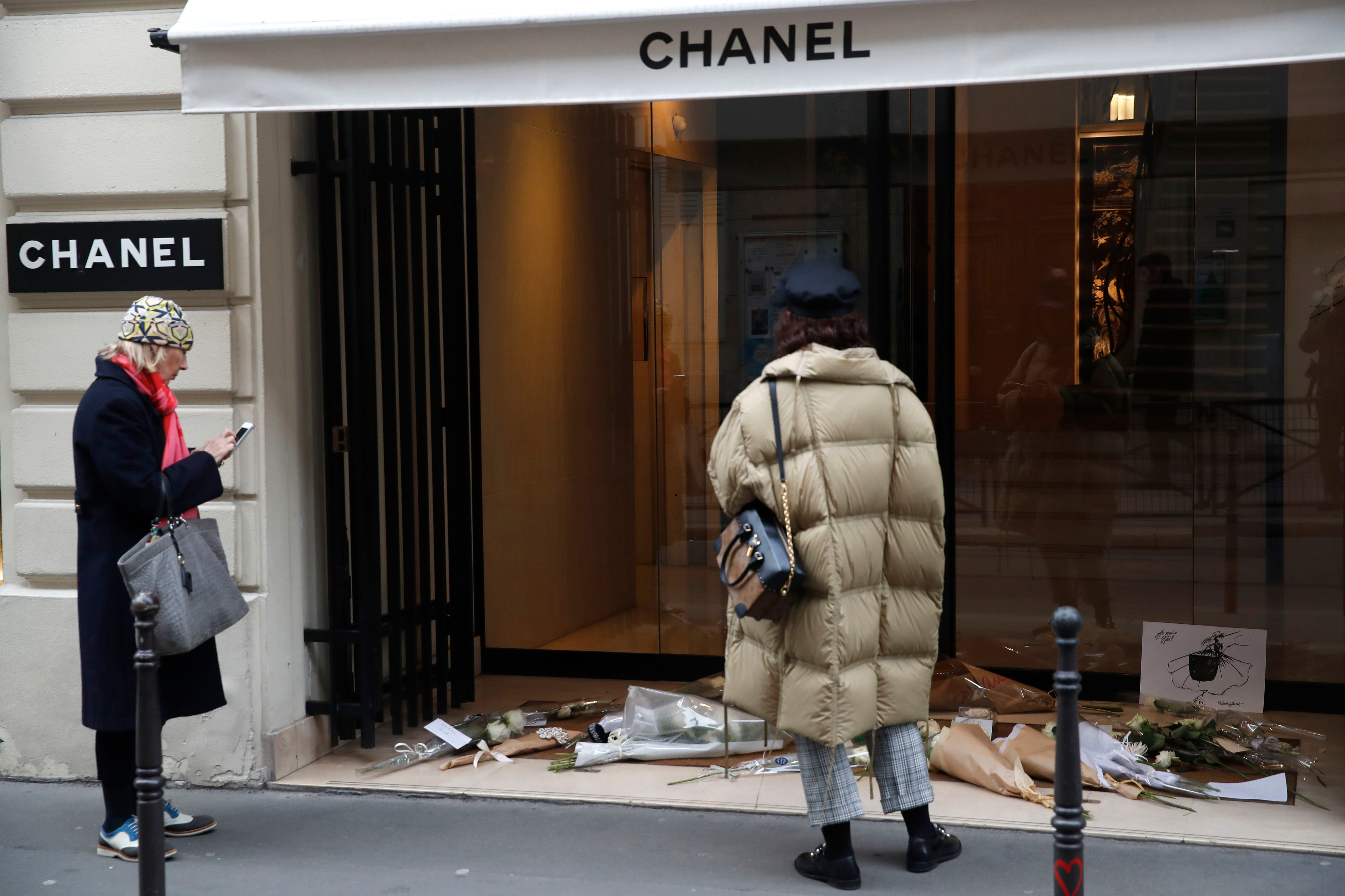 Women watch flowers at the entrance of Chanel headquarters in Paris, Wednesday, Feb.20, 2019. Karl Lagerfeld, the iconic couturier whose designs at Chanel and Fendi had an unprecedented impact on the entire fashion industry, died Tuesday in Paris, prompting an outpouring of love and admiration for the man whose career spanned six decadesObit Lagerfeld, Paris, France - 20 Feb 2019