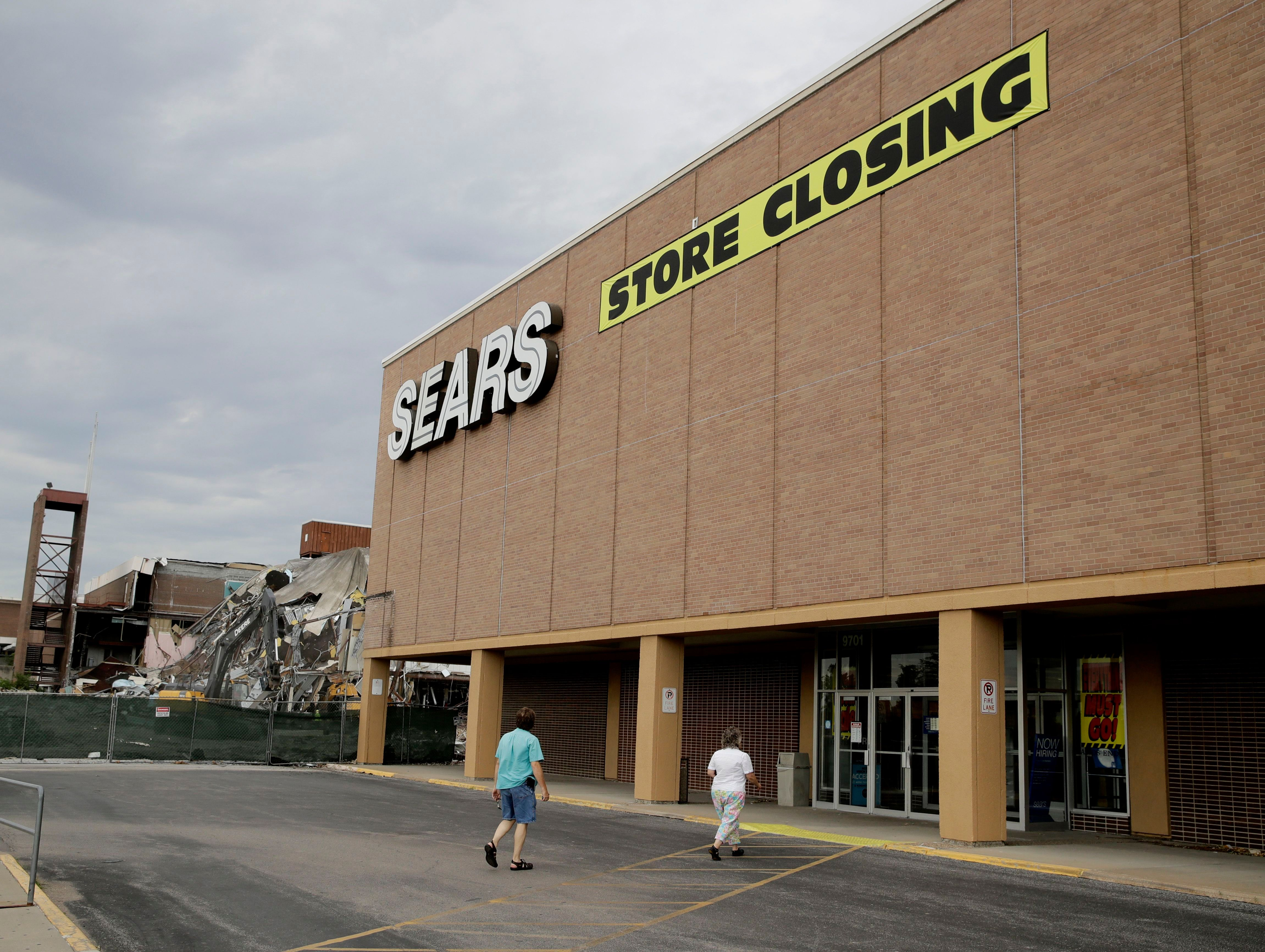 People walk into a Sears store slated for closing that is next to a mall that is being torn down in Overland Park, Kan. Sears has filed for Chapter 11 bankruptcy protection, buckling under its massive debt load and staggering losses. The company once dominated the American landscape, but whether a smaller Sears can be viable remains in questionSears, Overland Park, USA - 07 Jul 2017