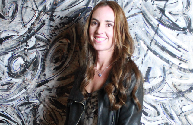 Andrea Tobin of Marla Cielo, standing in front of one of her canvases, to be made into handbags.