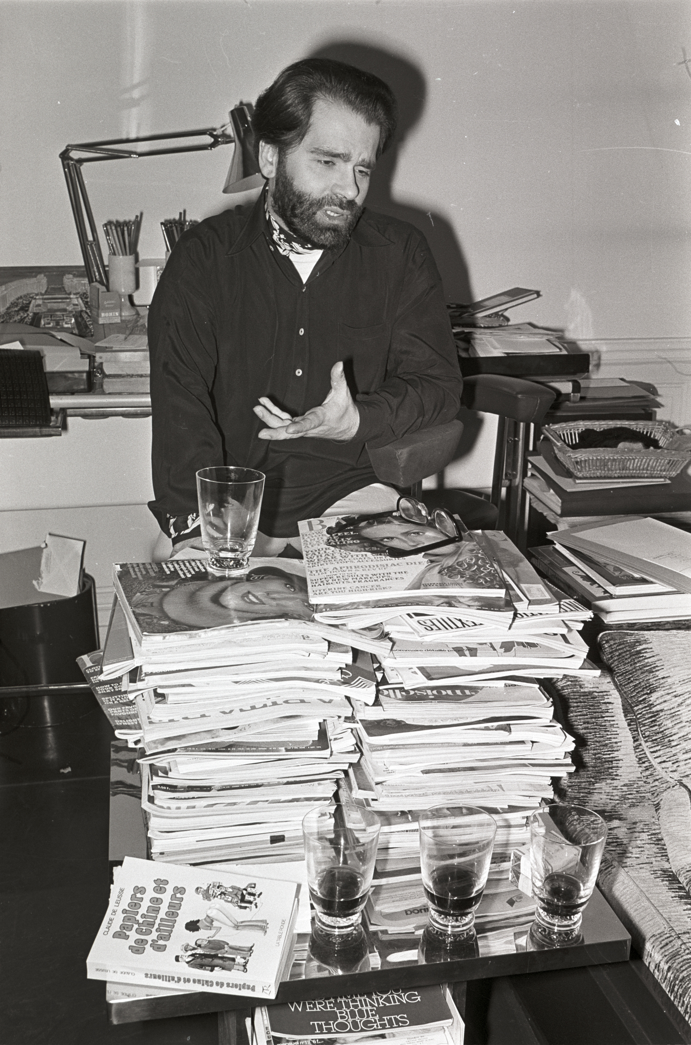 German fashion designer Karl Lagerfeld surrounded by stacks of fashion magazines at home